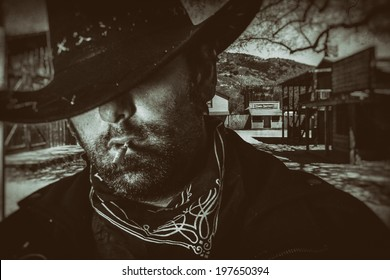 Old West Cowboy Western Town. An old west cowboy in a hat smoking a hand rolled cigarette with an old western town setting in the background, edited in vintage film style.