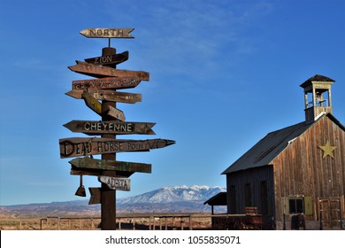 Old west wooden direction signs with old west school house and snow covered mountains in the background.  Utah.