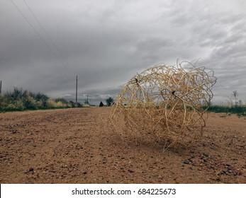 Old western tumbleweed blowing across dirt road