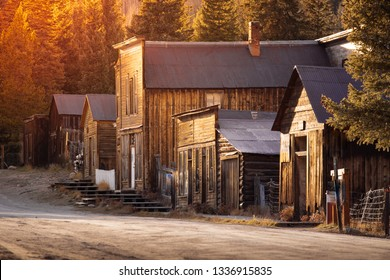 Old Western Wooden Buildings St. Elmo Gold Mine Ghost Town in Colorado, USA hidden in mountains, with yellow sun glow