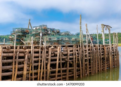 An old wharf filled with green metal lobster traps. The wharf is made from wooden logs, and is in mid tide water at the ocean. Partially cloudy sky above.