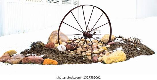 An old wheel on rocks, dirt, and snow a in Herriman, Utah neighborhood.