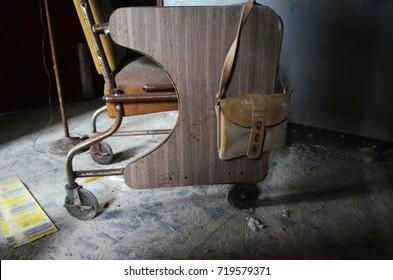 Old wheelchair inside of abandoned mental asylum hospital building