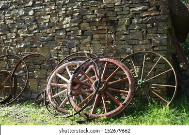 Old wheels by rural cottage wall.