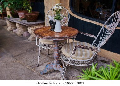 Old white antique wrought iron furniture, shabby chic exterior. Set of round table with flowers and two elegant chairs in the street in the old town. Table on cafe background. Vintage style.