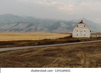 Old White Barn in Front of Beautiful Mountain Scenery