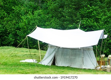 Old white big Bell tent standing on green meadow near forest. Vintage medieval tent by summer woods background