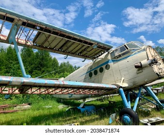 An old white and blue aircraft wreckage at a small airport in Laszki, Poland