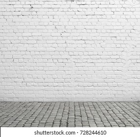 Old white brick wall and cobblestone floor.