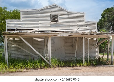 An old white building, falling apart, abandoned, made of wood siding, painted white with an attic window and closed shutters supported by 2x4 pillars supporting a porch roof located in South Louisiana