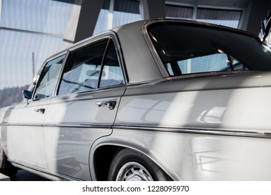 An old white car captures from behind that parked indoor with the windows in background.