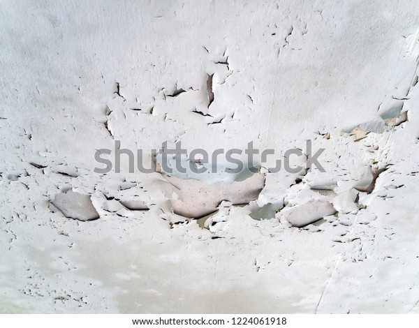 The old white ceiling is peeling off.
