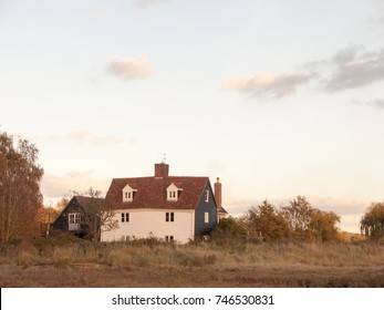 old white country farm house cottage in field; essex; england; uk