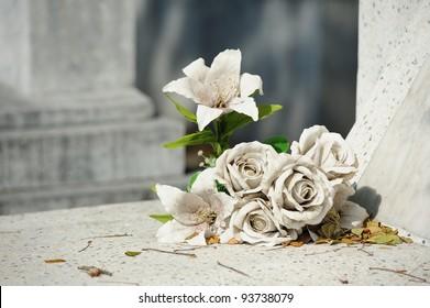 old white fake flower on grave