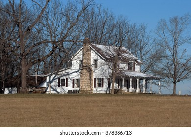 An old white farmhouse sitting among trees.