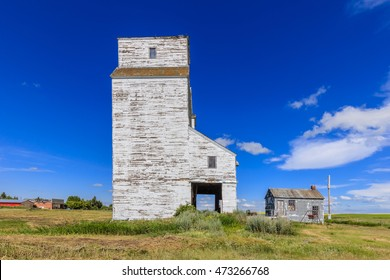 An old white grain elevator in a small town in the Canadian prairies.