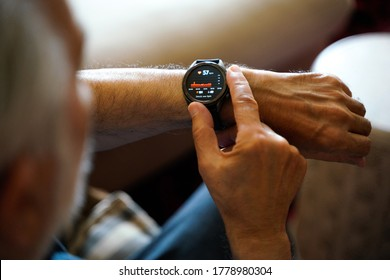 old white haired man using smart watch checking his cardiogram ecg