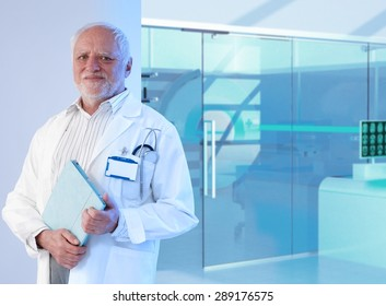 Old white haired professor doctor standing in front of MRI room at hospital, holding tablet, smiling.
