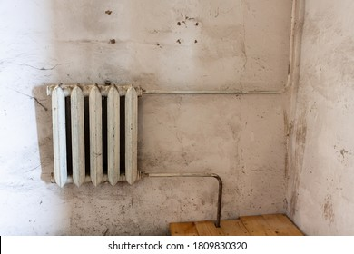 old white heating radiator on a white dirty wall. old heating system