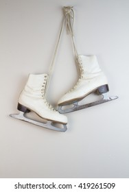 Old white ice skates hanging on the wall