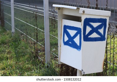 Old white metal post box (letterbox, mailbox) stand close (near) wire fence for send/deliver letter. Two (2) big symbol (icon) of letters painted by blue color with brush. Long perspective side view.