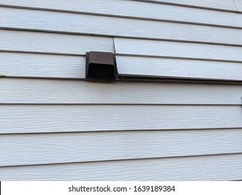 Old white metal siding on the back of a house coming loose near a dryer vent and needing repairs or replacement and renovations