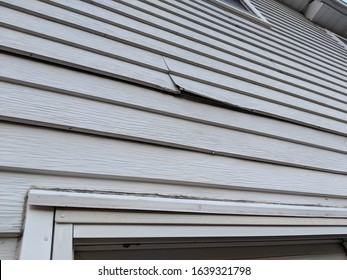 Old white metal siding on the back of a house coming loose near windows and needing repairs or replacement and renovations