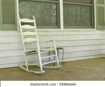 An old white painted wooden rocking chair sitting outside on a dirty front porch