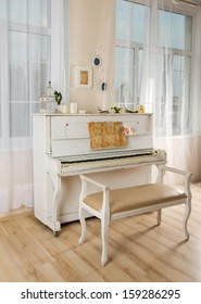 Old white piano and chair in a living room