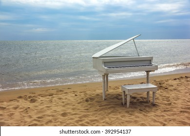 Old white piano on a sandy beach.  Beidaihe, China
