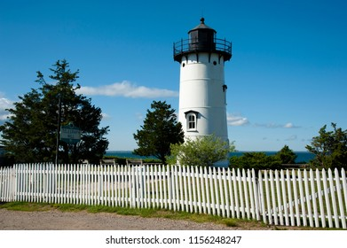 An old white picket fence surrounds East Chop lighthouse tower, on Telegraph Hill, on Martha's Vineyard Island. It is a popular attraction for the many tourists who come to the island.