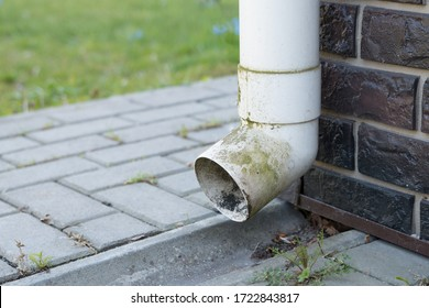 Old white plastic drain pipe on the brown brick wall. Downspout