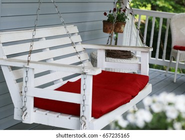 Old white porch swing with red cushions