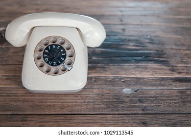 old white rotary telephone on wood table