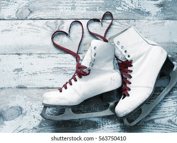 Old white skates for figure skating with a hearts of laces on a vintage wooden surface. Concept of love