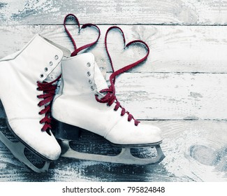 Old white skates for figure skating with a hearts of laces on a vintage wooden surface. Concept of love.