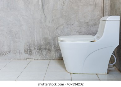 Old of white toilet bowl near the wall in bathroom