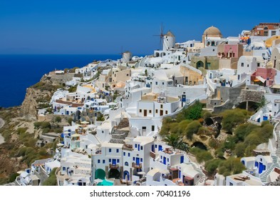 Old white traditional windmills in terraced village Oia of Cyclades island Santorini, Greece. And blue Aegean Sea and sky background.