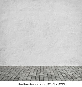 Old white wall and cobblestone floor.