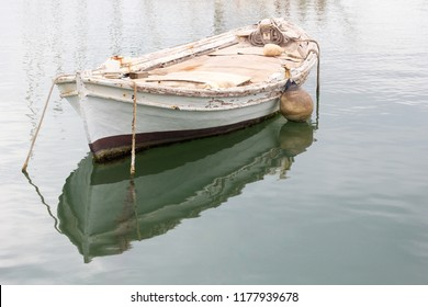 Old white weathered wooden rowing boat or dinghy moored in a harbour in Greece.