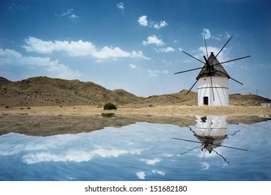 Old white windmill in Spain with reflection