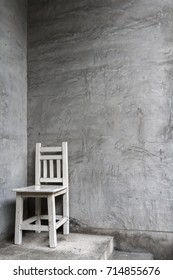 Old white wooden chair put on concrete floor and in front of dirty cement wall, Still life image and under roof lighting background