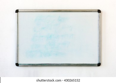 Old whiteboard for office with traces of stains and spots. Writing board hanging on the old dirty wall in the office.