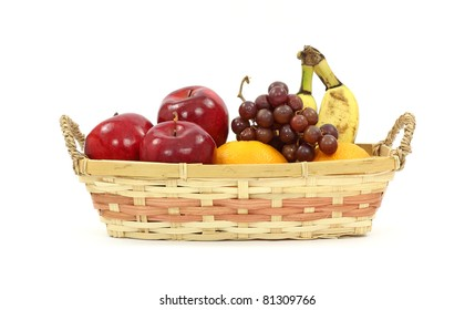 An old wicker basket with apples oranges grapes and bananas on a white background.