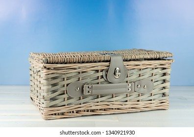 Old wicker basket on wooden table, blue sky background