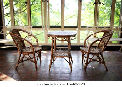 An old wicker bistro table and chair set sits empty in a sun room patio of a large historic house.