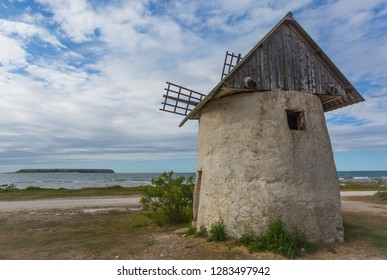 An old wind mill, Gotland style, on the Ekstakusten of Gotland in the Baltic sea, with the bird Island, the big Karlso, in the background