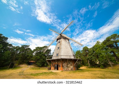 Old wind mill at the park with blue sky clouds