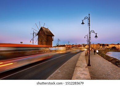Old windmill in the ancient town of Nesebar in Bulgaria.The entrance to the old town. Bulgarian Black Sea coast. UNESCO world heritage site. Road, night lights. Car light trails. Long exposure