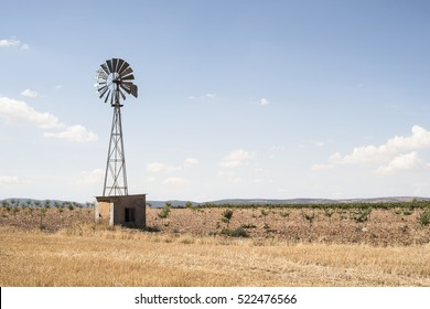 Old windmill at blue cloudy sky